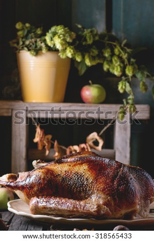 Roast stuffed goose on ceramic plate with ripe apples over wooden kitchen table. Dark rustic style.  - stock photo