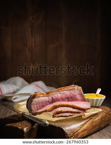 Roast topside of beef sliced on rustic board with pot of mustard - stock photo