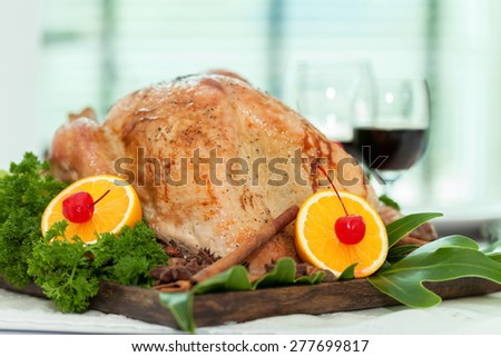Roast Turkey with vegetables in wooden tray. - stock photo
