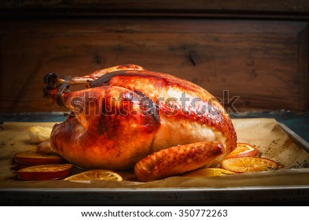 Roast whole turkey or chicken over wooden background, side view - stock photo
