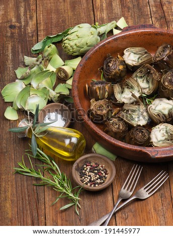 roasted and fresh  artichokes with olive oil, pepper and salt on the wooden table  - stock photo