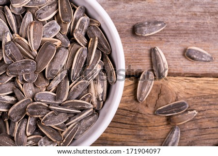 Roasted and salted sunflowers seeds in their shells, in white ceramic bowl over old wood background. - stock photo