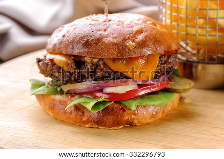 roasted beef hamburger with cheese and vegetables close-up on wooden board  - stock photo