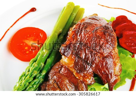 roasted beef meat served with asparagus on plate - stock photo