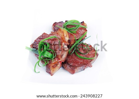 roasted beef meat strips steak on white ceramic plate isolated over white background - stock photo