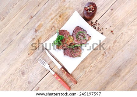 roasted beef meat strips steak on white ceramic plate with hot dry pepper on wood table - stock photo