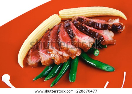 roasted beef meat with beans and corns on red plate - stock photo