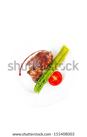 roasted beef served with asparagus on white dish - stock photo