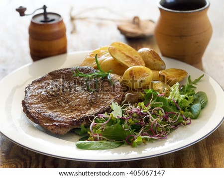 Roasted beef steak with baked potatoes and green salad  - stock photo