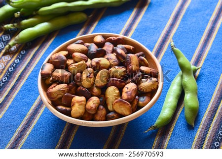 Roasted broad beans (lat. Vicia faba) eaten as snack in Bolivia in bowl with fresh broad bean pods on blue fabric, photographed with natural light (Selective Focus, Focus the middle of roasted beans) - stock photo
