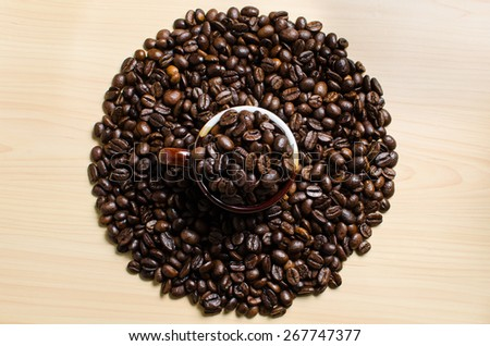 Roasted brown coffee beans & mug  on wooden table - stock photo