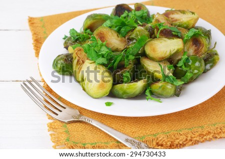 Roasted Brussels sprouts with chopped parsley in white plate with napkin on white wooden table. - stock photo