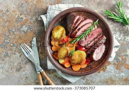 Roasted carrots, potato and cut meat, plain rustic dish - stock photo
