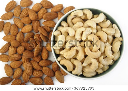 roasted cashew nuts in bowl and raw almond - stock photo
