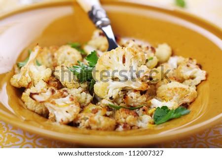 Roasted cauliflower with lemon peel and garlic. - stock photo