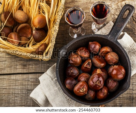 Roasted chestnuts in a cast iron skillet on a wooden surface - stock photo