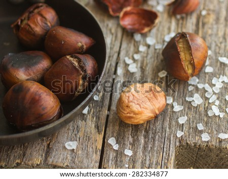 Roasted chestnuts on wooden table with coarse salt - stock photo