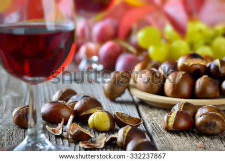 Roasted chestnuts with South Tyrolean red wine on an old wooden table, wine grapes in the background - stock photo