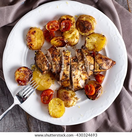 Roasted chicken breast in honey-balsamic marinade with potatoes and cherry tomatoes on white plate and wood background - stock photo
