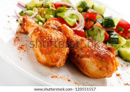 Roasted chicken drumsticks and vegetables - stock photo