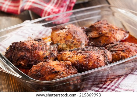 Roasted chicken drumsticks in casserole dish. Selective focus - stock photo
