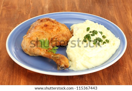 roasted chicken leg with mashed potato in the plate on wooden table close-up - stock photo