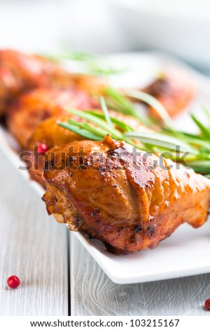 Roasted chicken legs flavored with rosemary and pink pepper - stock photo
