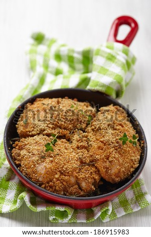 roasted chicken legs with bread crust, cheese and herbs - stock photo
