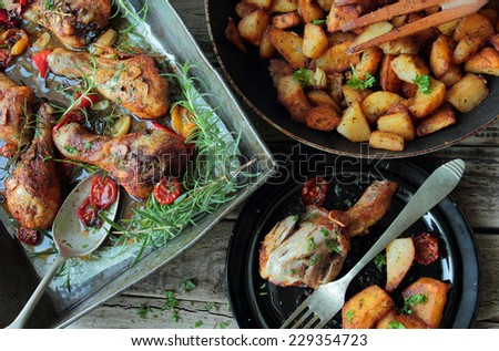 Roasted chicken legs with fried potatoes and aromatic herbs - stock photo