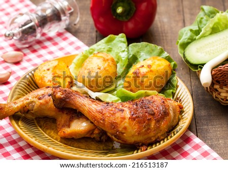 Roasted chicken legs with potato and salad - stock photo