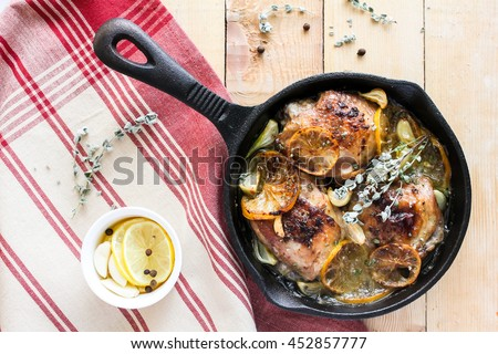Roasted chicken meat with lemon slices, garlic cloves, thyme and black peppercorns in a pan on a wooden table, top view, selective focus - stock photo