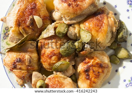 Roasted chicken thighs on a plate, pickles, olives. Close-up. - stock photo