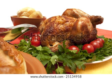 Roasted chicken (turkey) garnished with tomatoes, bread and potatoes on holiday table ready to eat - stock photo