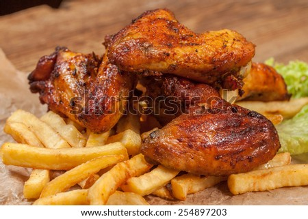 Roasted chicken wings and chips. - stock photo