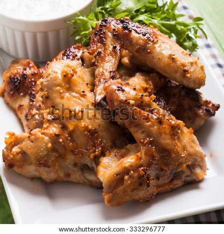 Roasted Chicken wings and tzatziki sauce on a plate - stock photo