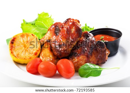 Roasted chicken wings and vegetables on plate - stock photo