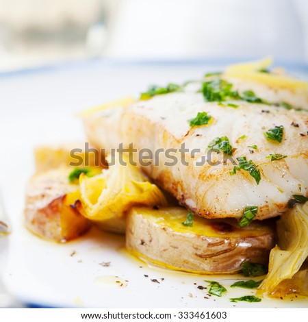 Roasted cod, codfish with baked potatoes and artichokes with lemon and herbs sauce on a white background Restaurant serving - stock photo