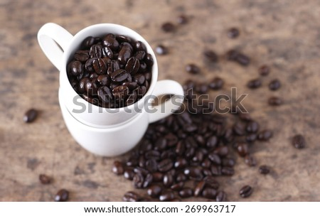 roasted coffee bean in stack of white coffee cup on wooden background (selective focus) - stock photo
