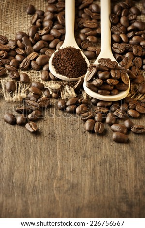 Roasted coffee beans and ground coffee in wooden spoons on coffee heap. Shallow DOF. - stock photo