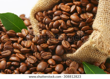 Roasted coffee beans in a burlap sack - stock photo