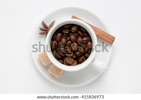 Roasted coffee beans in a coffee cup on saucer decorated star anise, cinnamon stick and cane sugar cubes against white background. Top view with space for text. Symbol of fresh flavored coffee. - stock photo