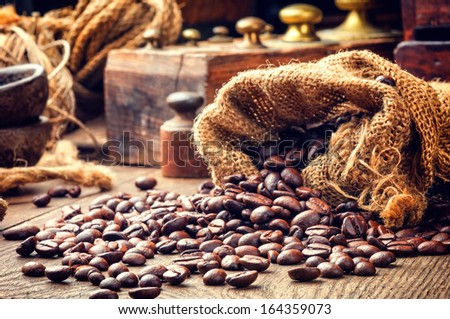 Roasted coffee beans in toned vintage setting - stock photo