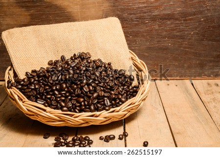 roasted coffee beans in wicker basket, close-up  - stock photo
