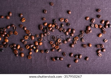 Roasted coffee beans on grey textile background - stock photo