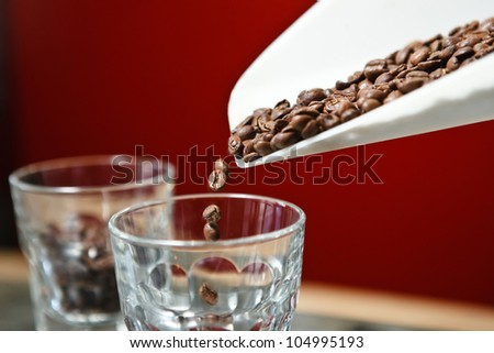 Roasted coffee beans pouring in glass - stock photo
