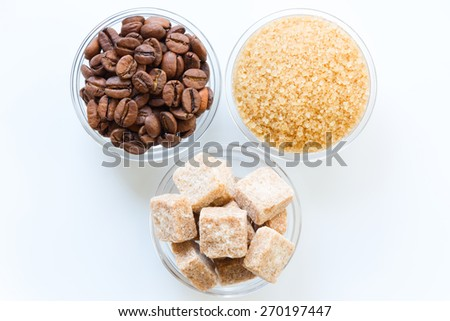 Roasted coffee beans, raw sugar cubes, and brown sugar in the glass bowls isolated - stock photo