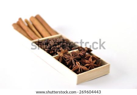 Roasted coffee beans with cinnamon sticks and star anise seeds in a wooden tray isolated on white background. - stock photo
