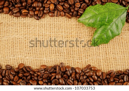 Roasted coffee beans with leaves on jute background - stock photo