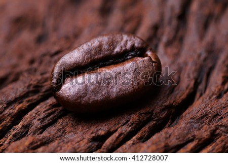 Roasted detailed tasty coffee bean with natural wooden background. - stock photo