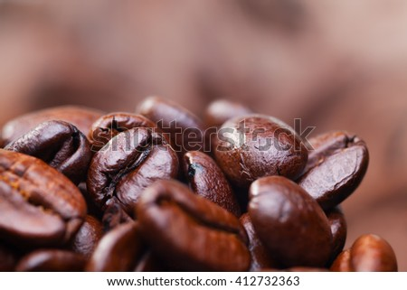 Roasted detailed tasty coffee beans with natural blurry background. - stock photo
